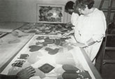 Miriam Schapiro (right), assisted by Liz Jordan, applies collage elements to Children of Paradise, 1984